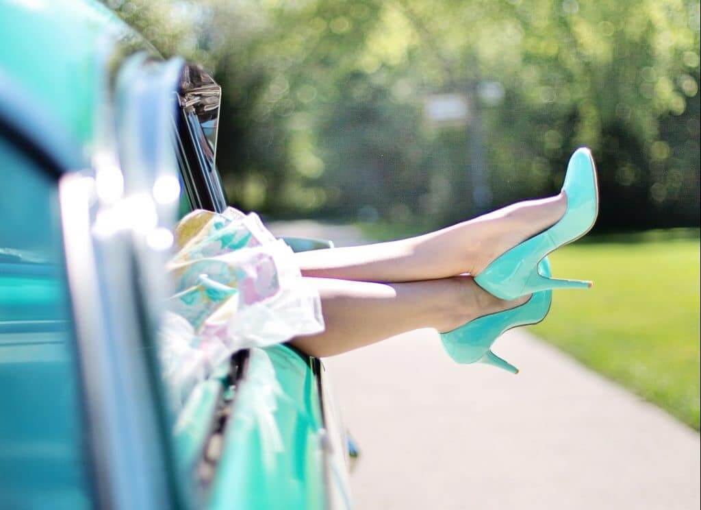 Womans legs with high heels sticking out of car window