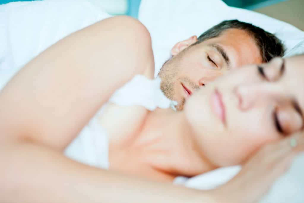 couple in bed sleeping with a weighted blanket