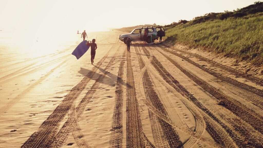 family with jeep and wetsuits and boogieboards playing at the beach