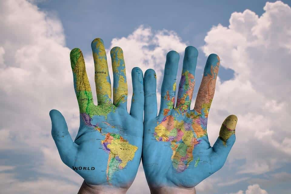 painted hands showing the world