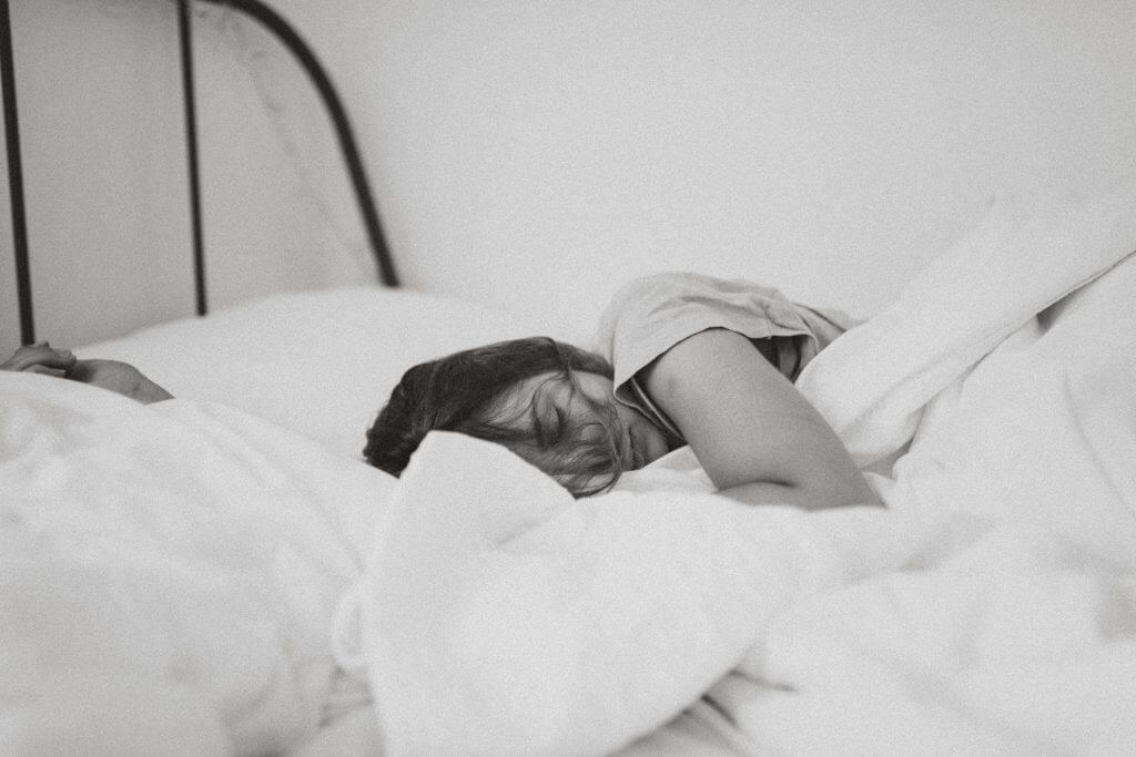 Woman in bed sleeping with white blankets